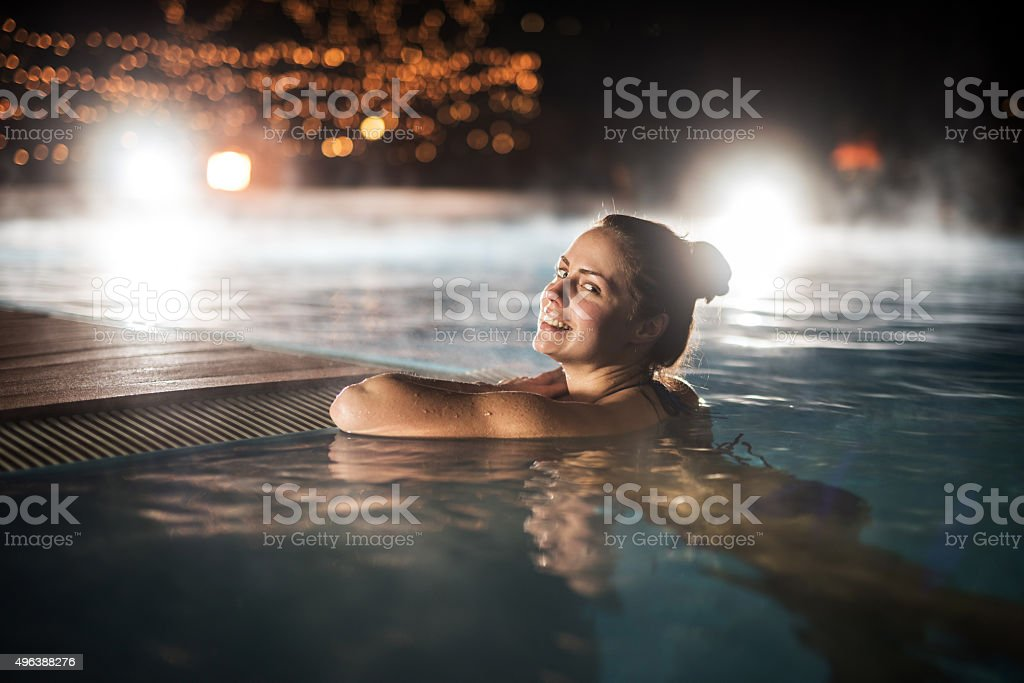 Happy woman relaxing in heated swimming pool during winter night. stock photo