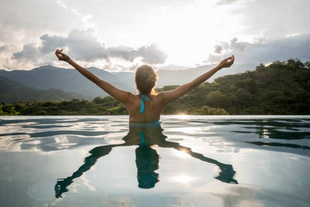 feliz mujer relajante en la piscina con los brazos arriba - viaje a sudamérica fotografías e imágenes de stock