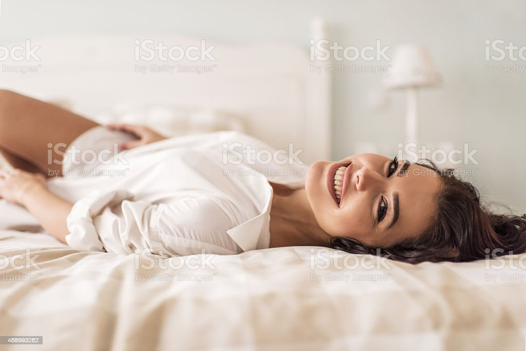 Happy woman relaxing on a bed and looking at camera. stock photo