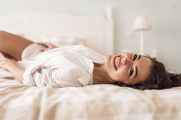 happy woman relaxing on a bed and looking at camera. - reclining stock photos and pictures
