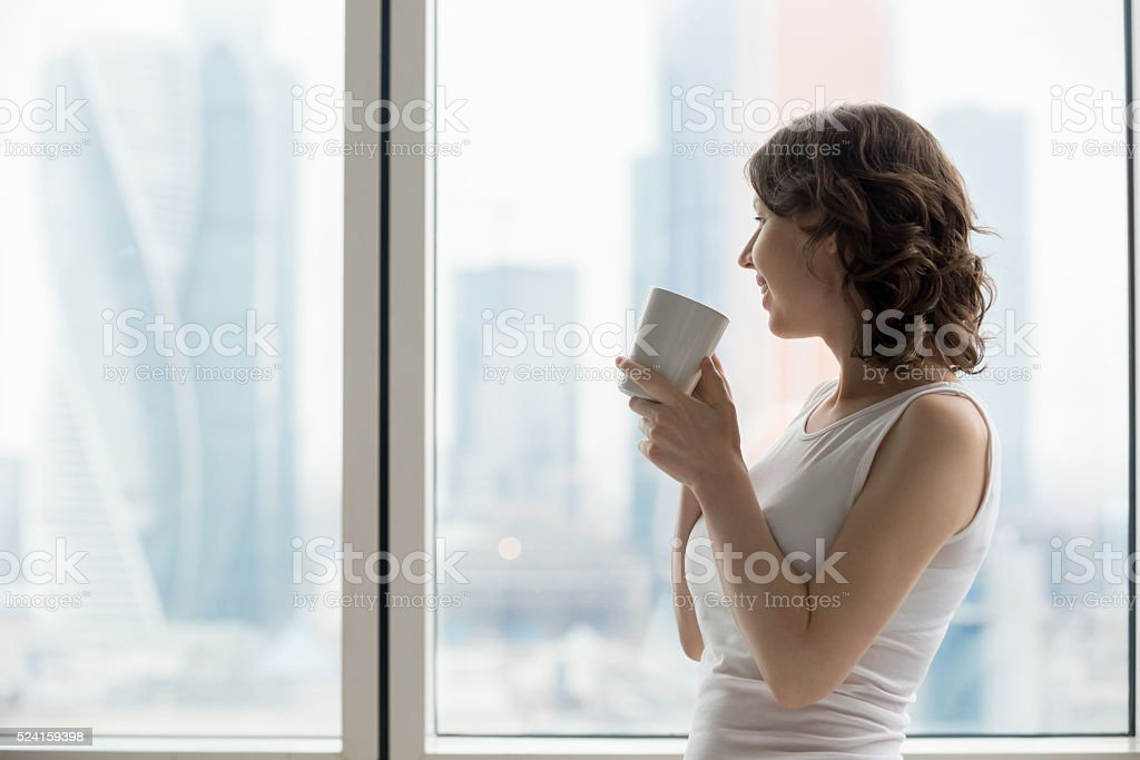 Happy woman relaxing with hot drink stock photo