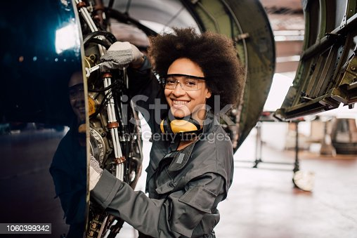 Happy young mechanic repairing airplane