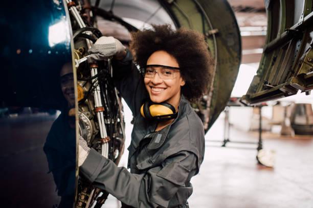 gelukkige vrouw herstellen van vliegtuigen - luchtvaartindustrie stockfoto's en -beelden