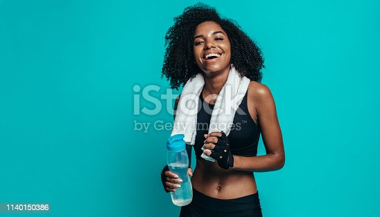 Happy young woman resting after workout on blue background. Healthy young female taking a break after exercising.