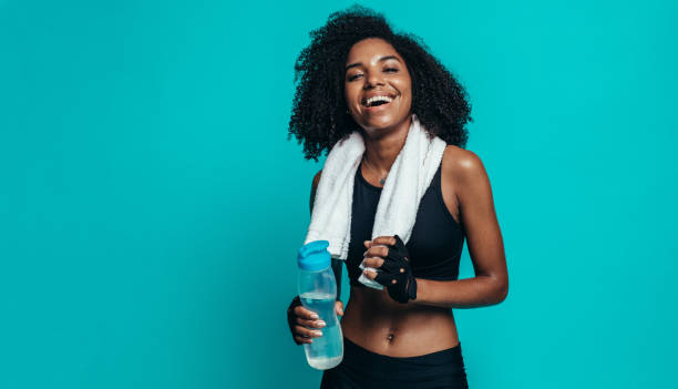 Happy woman resting after workout Happy young woman resting after workout on blue background. Healthy young female taking a break after exercising. exercising stock pictures, royalty-free photos & images