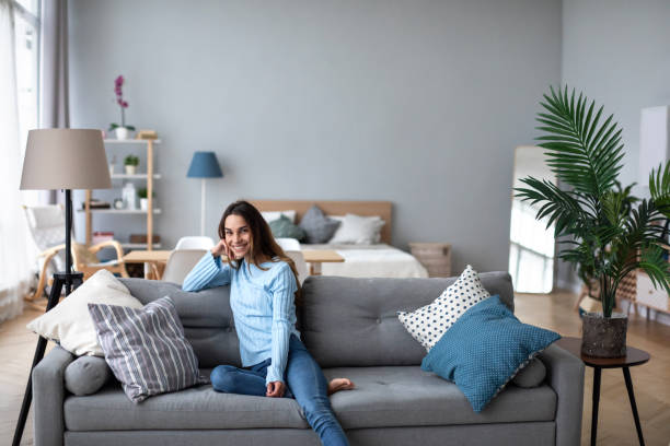 Happy woman resting comfortably sitting on sofa in the living room at home. stock photo