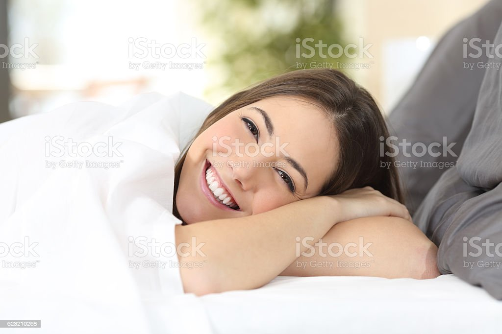 Happy woman resting in a comfortable bed stock photo
