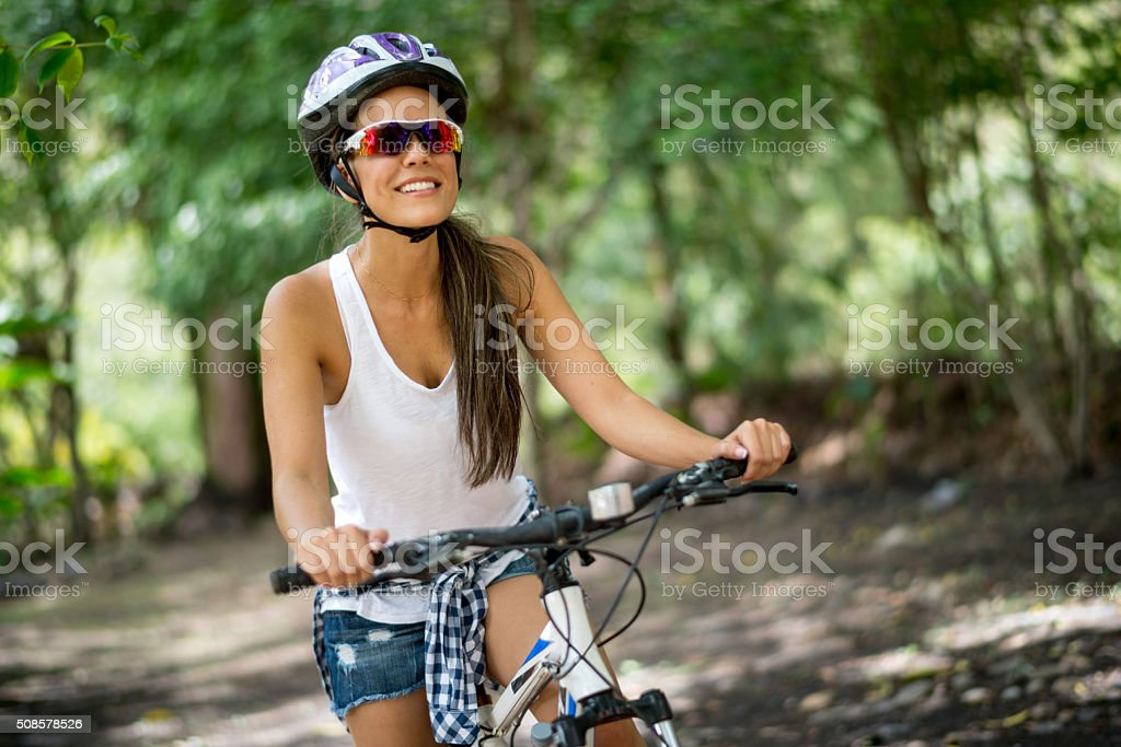 Happy woman riding a mountain bike stock photo