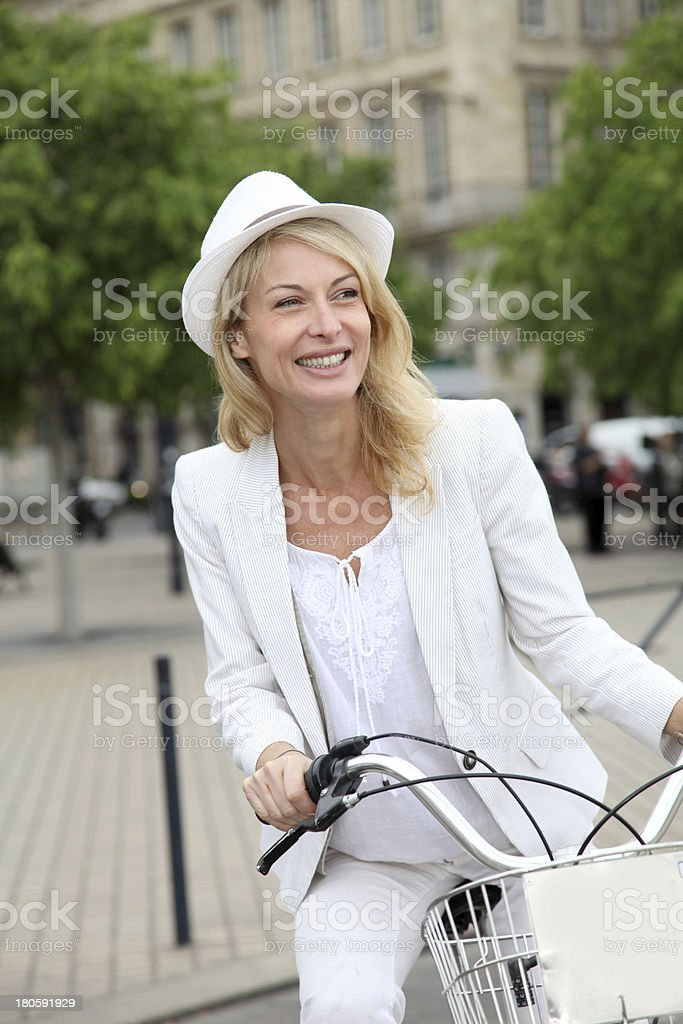 Happy woman riding bicycle to visit city royalty-free stock photo