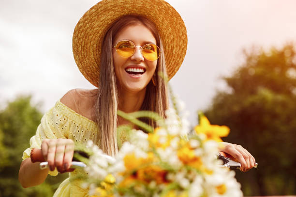 Happy woman riding bicycle with flowers stock photo