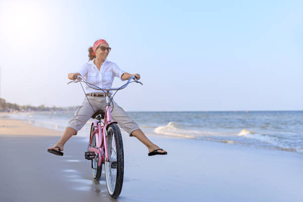Happy woman riding bike on beach stock photo