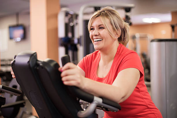 Happy woman riding on exercise bike at the gym Happy woman riding on exercise bike at the gym exercise bike stock pictures, royalty-free photos & images