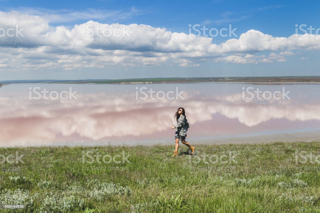 Happy woman running by the lake shore in springtime. Grey cardigan and long black hair stock photo