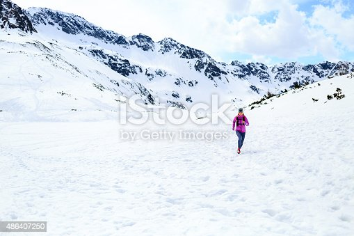484750230 istock photo Happy woman running in mountains on winter sunny day 486407250