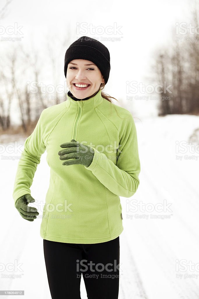 Happy woman running in winter stock photo