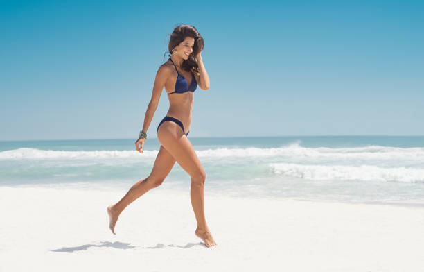 Happy woman running on beach Happy smiling woman jumping on the beach. Beautiful young woman running on tropical beach. Happy latin girl walking on white sand beach during summer vacation with copy space. bikini stock pictures, royalty-free photos & images