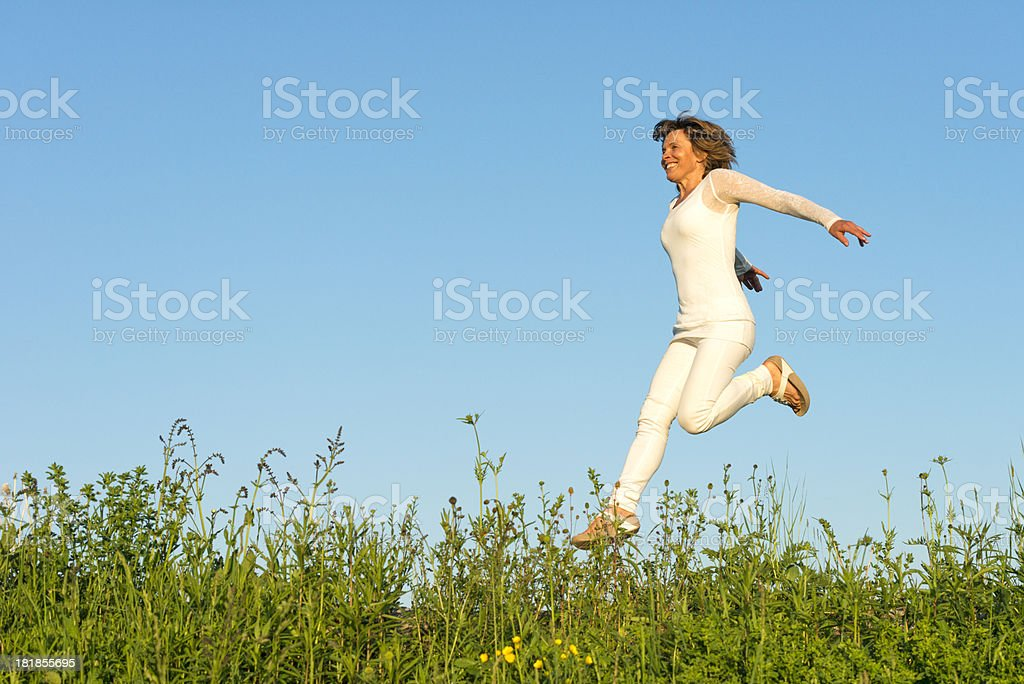 happy woman running on meadow royalty-free stock photo
