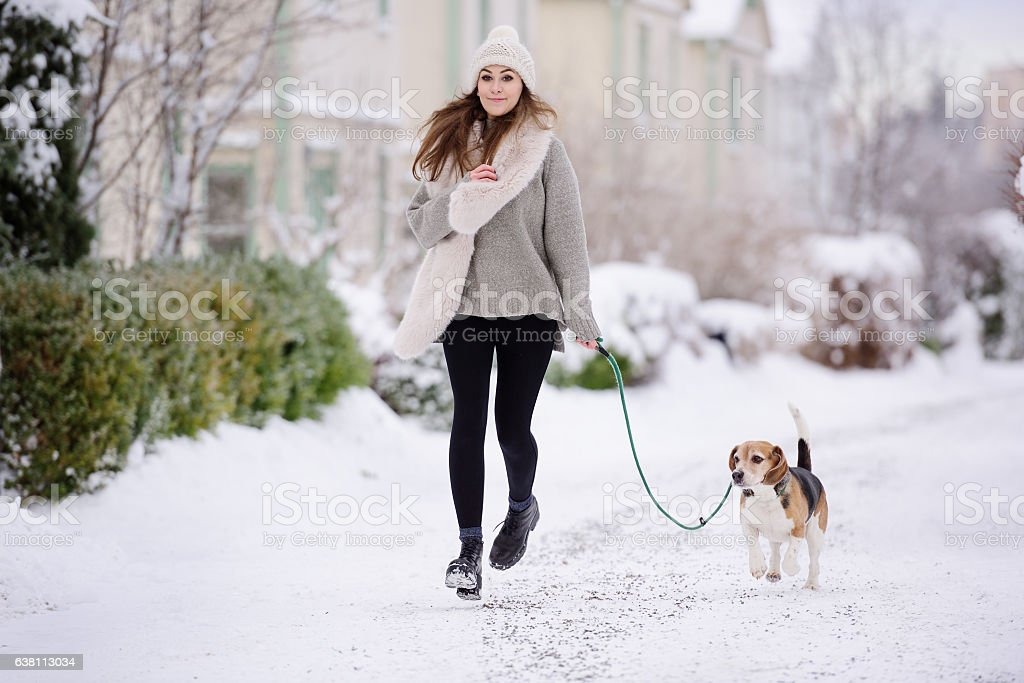 Happy woman running with beagle dog on winter street stock photo