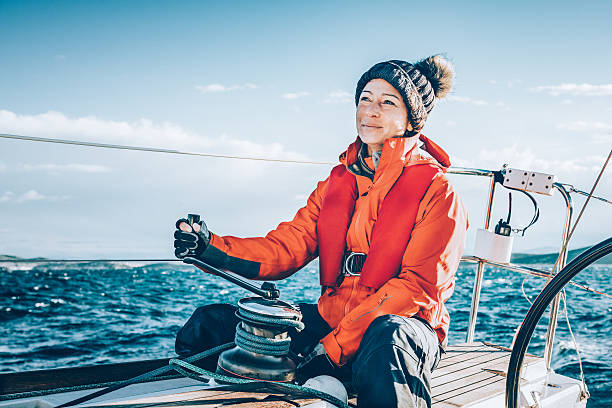 Happy woman sailing during regatta Happy woman sailor sailing as main sail trimmer during regatta. sailor stock pictures, royalty-free photos & images
