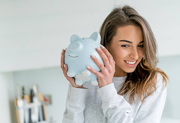 Happy woman saving money in a piggybank - Photo