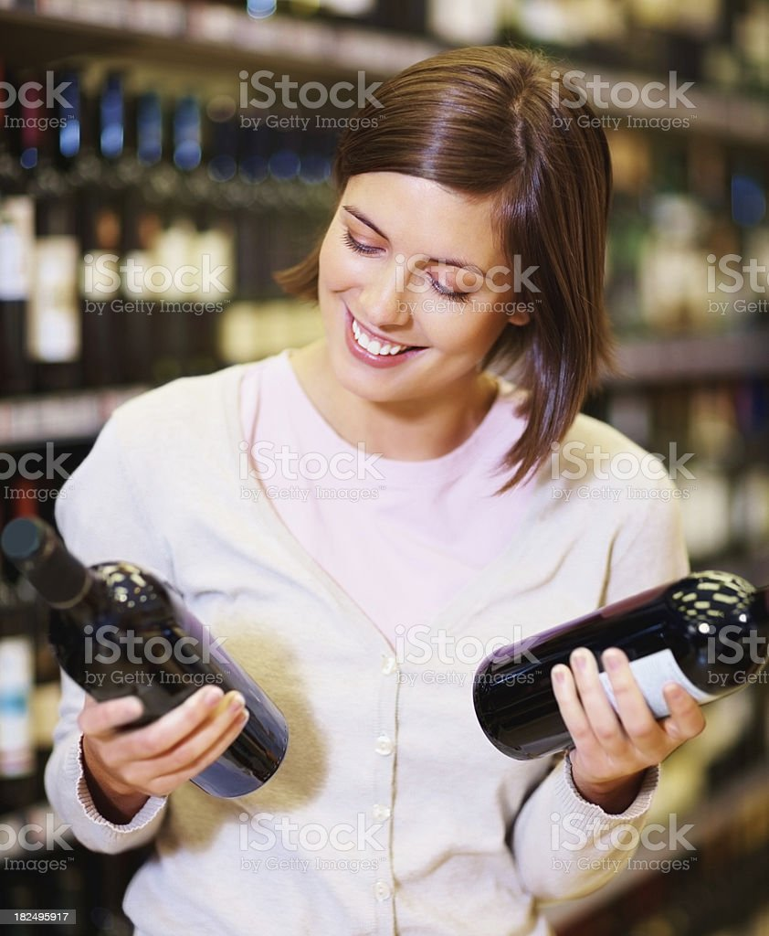 Happy woman selecting wine bottles at supermarket royalty-free stock photo
