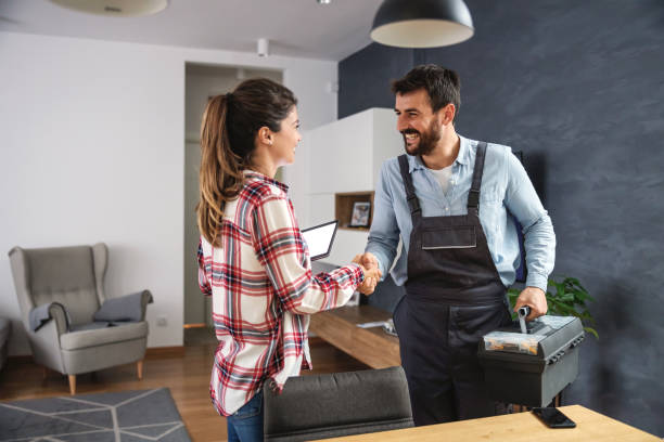 Happy woman shaking hands with repairman. Home interior. stock photo