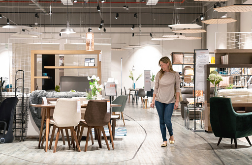 Happy woman shopping at a furniture store and looking at a dining room while smiling - lifestyle concepts