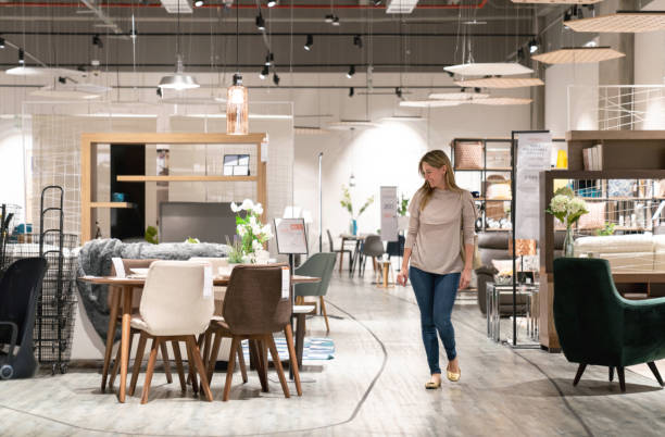 happy woman shopping at a furniture store - furniture shopping stock photos and pictures