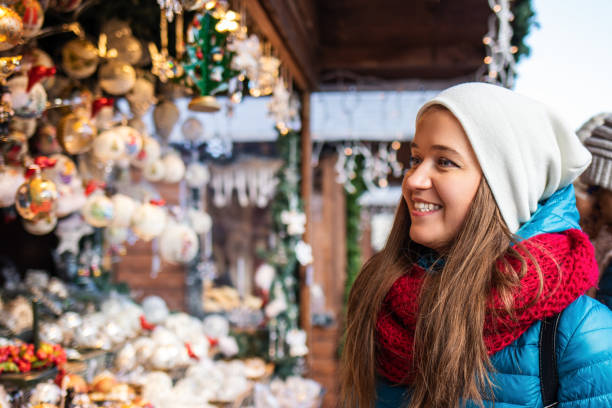 Happy woman shopping christmas decoration at market stall stock photo
