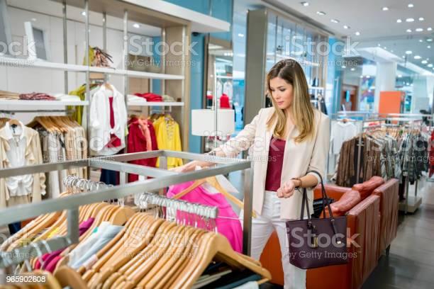 Happy Woman Shopping For Clothes At A Store - Fotografias de stock e mais imagens de 20-29 Anos