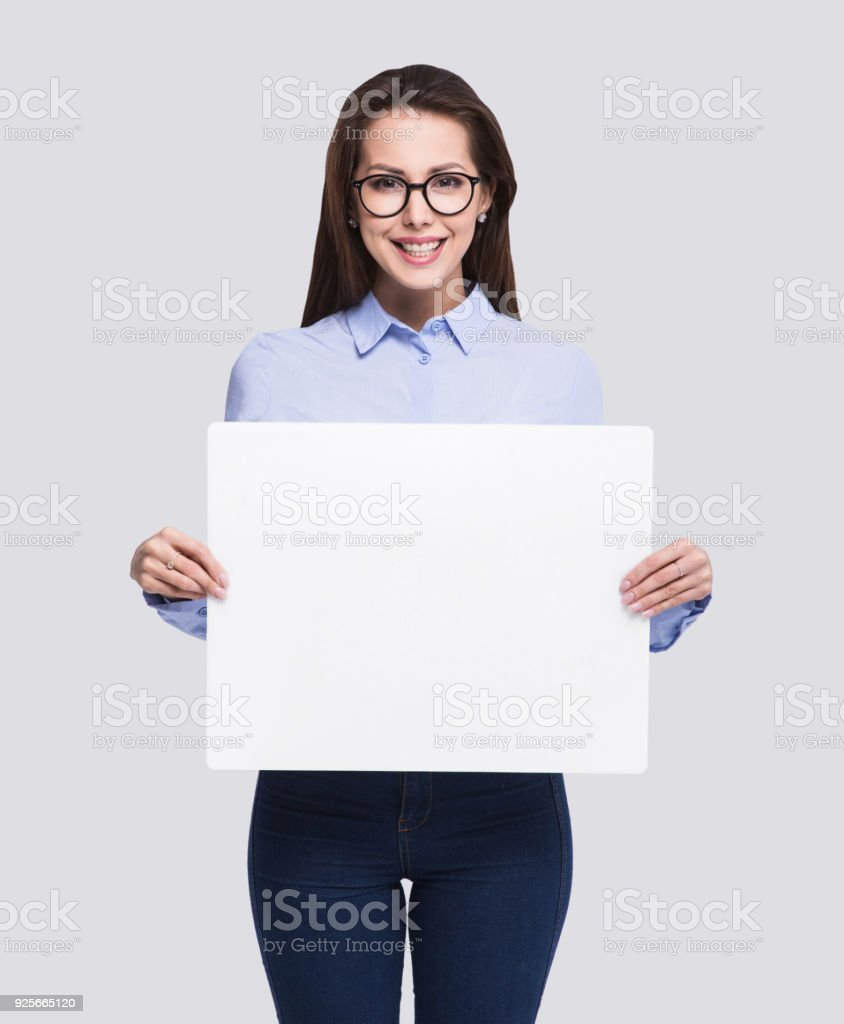Happy woman showing blank white banner stock photo