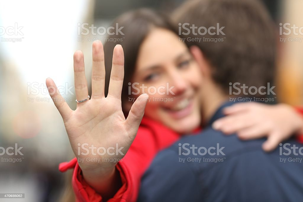 Happy woman showing engagement ring after proposal stock photo
