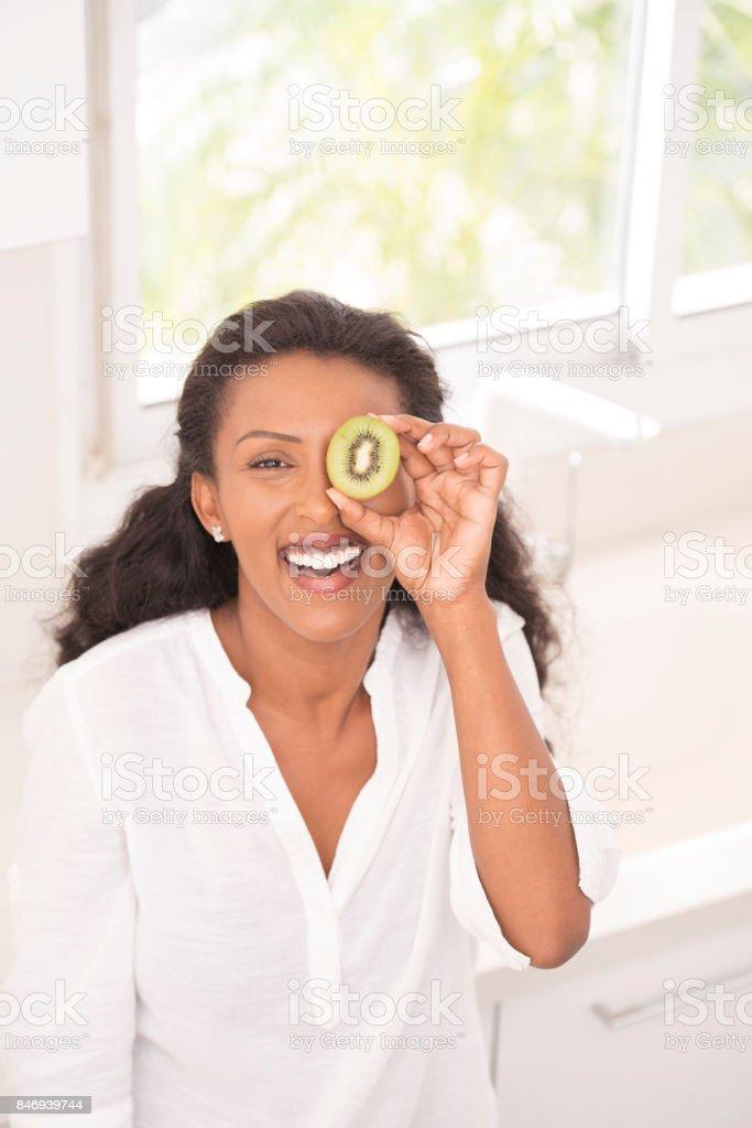 Happy woman showing halved kiwi fruit. stock photo