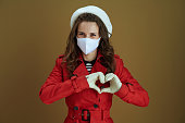 Life during covid-19 pandemic. Portrait of happy stylish 40 years old housewife in red coat showing heart shaped hands isolated on bronze background.