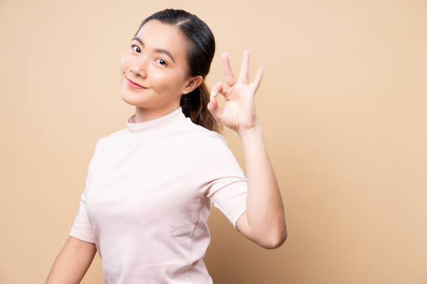 Happy woman showing OK gesture isolated on background stock photo