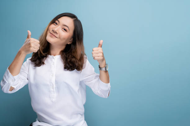 Happy woman showing thumb up isolated on background stock photo