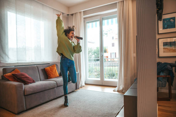 Happy woman singing in the living room stock photo
