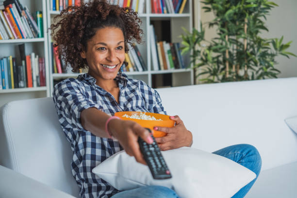Happy woman sitting at home with remote control watching tv stock photo