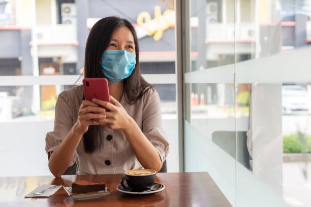 幸せな女性は、携帯電話でカフェに座って、外を見て、笑顔 - business malaysia ストックフォトと画像