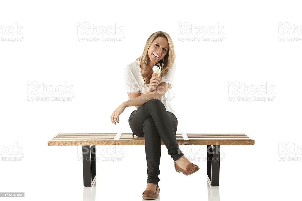Happy woman sitting on a bench and eating ice cream stock photo