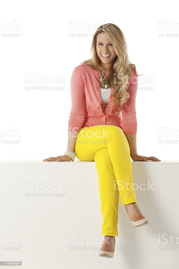 Happy woman sitting on a ledge stock photo