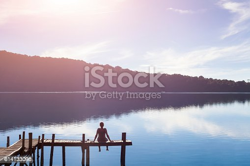 istock Happy woman sitting on a pier getting inspired by nature 614133098