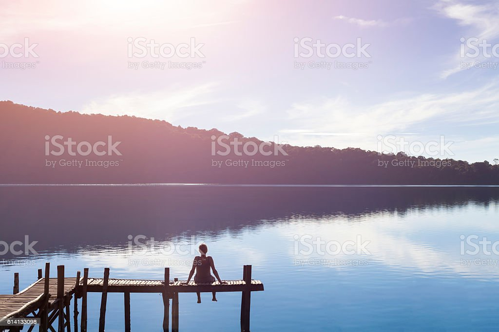 Happy woman sitting on a pier getting inspired by nature stock photo