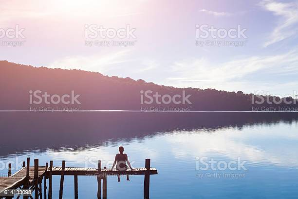 Photo of Happy woman sitting on a pier getting inspired by nature