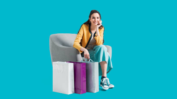 Happy woman sitting on an armchair after shopping stock photo