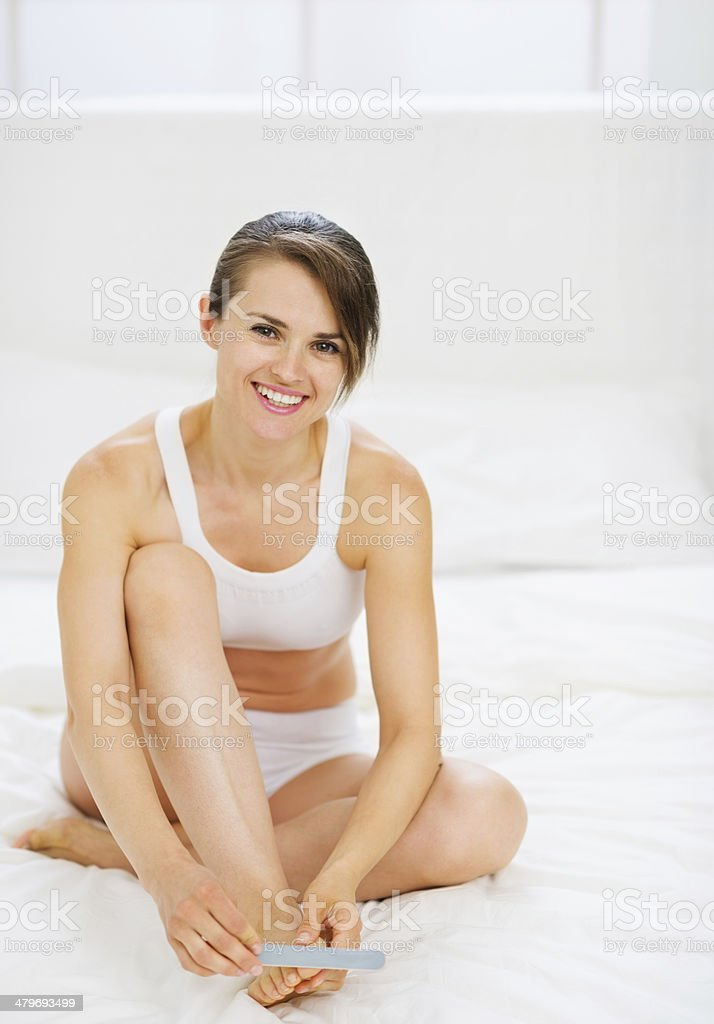 happy woman sitting on bed and making manicure stock photo