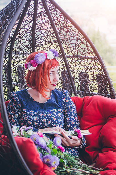 happy woman sitting on swing chair and reading book - hippie wohnkultur stock-fotos und bilder