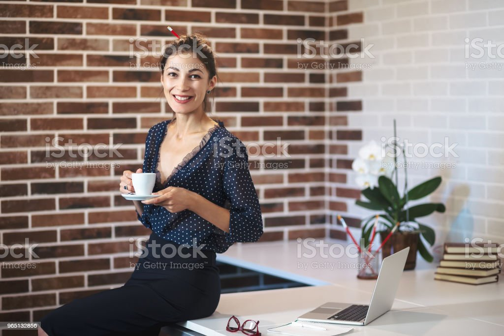 Happy woman sitting on the desk with a cup of coffee royalty-free stock photo