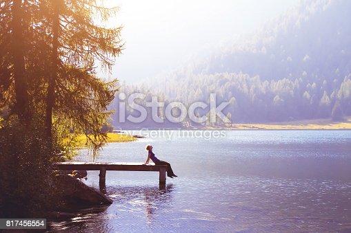istock happy woman sitting on the pier 817456554