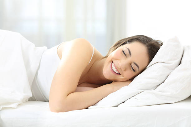 Happy woman sleeping comfortable in a bed stock photo